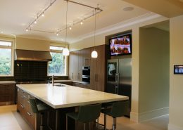 Luxury kitchen with wall mounted TV, in-ceiling speakers and touchscreen control