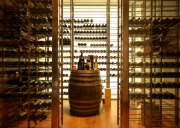 Wine bottles on barrel in a custom wine cellar featuring lighting, refrigeration and humidity control