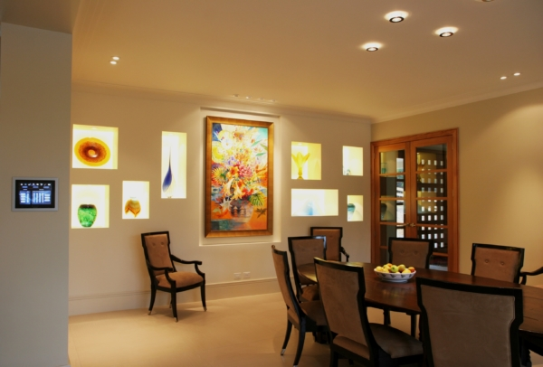Dining room with feature art wall enhanced by lighting controlled by touchscreen panel