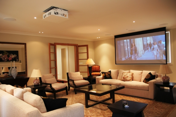 Comfortable home theatre with projector screen and in-ceiling speakers