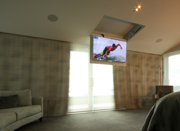 A motorized drop down TV mount helps to hide the screen in the ceiling
